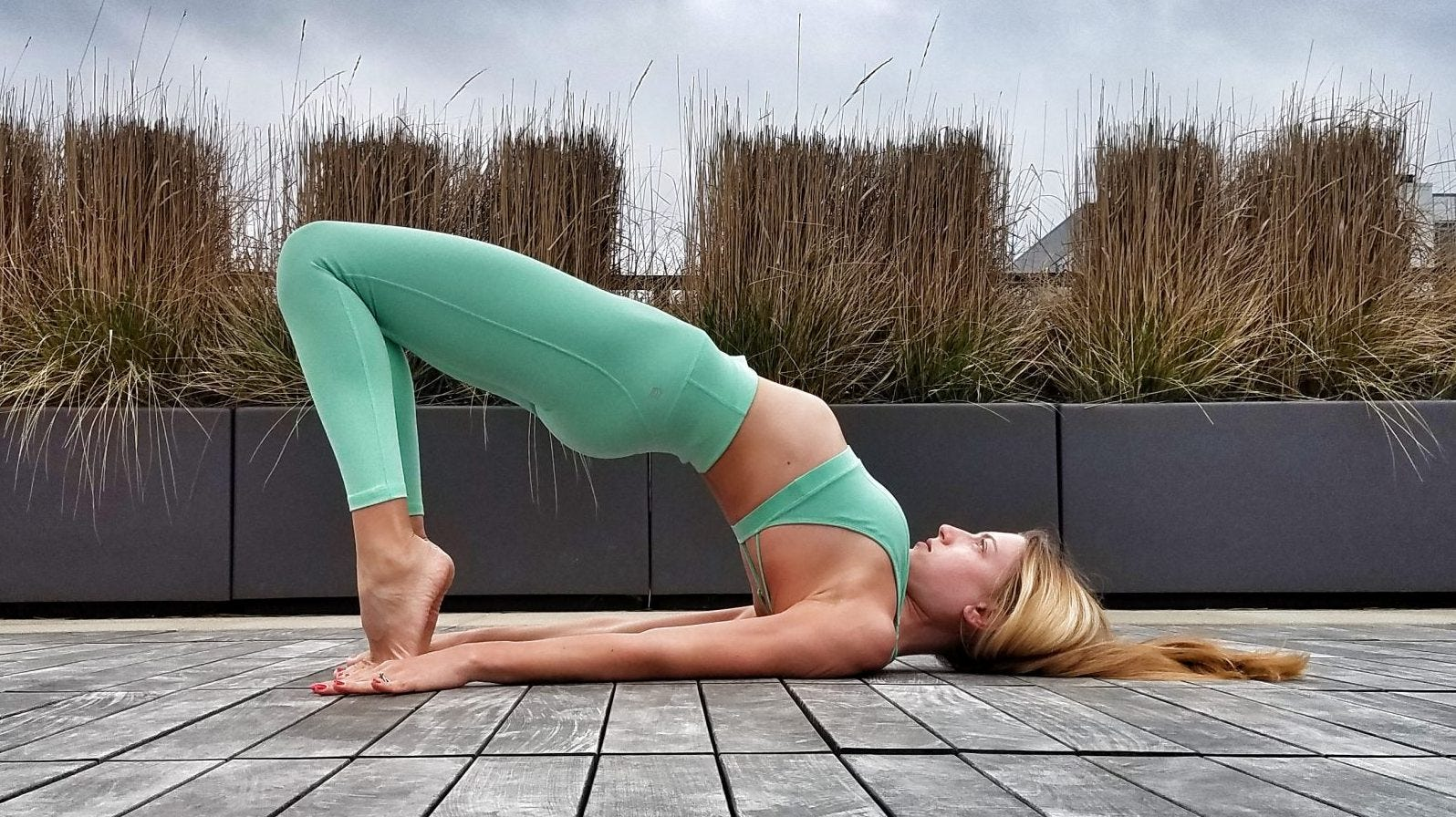 Woman doing yoga bridge pose next to ornamental grasses