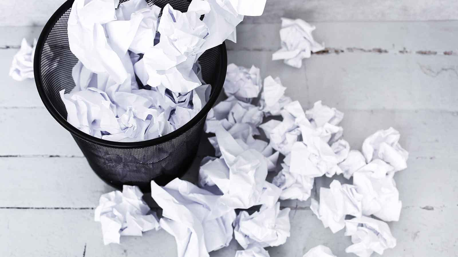 Trash can full of crumpled and scattered paper.