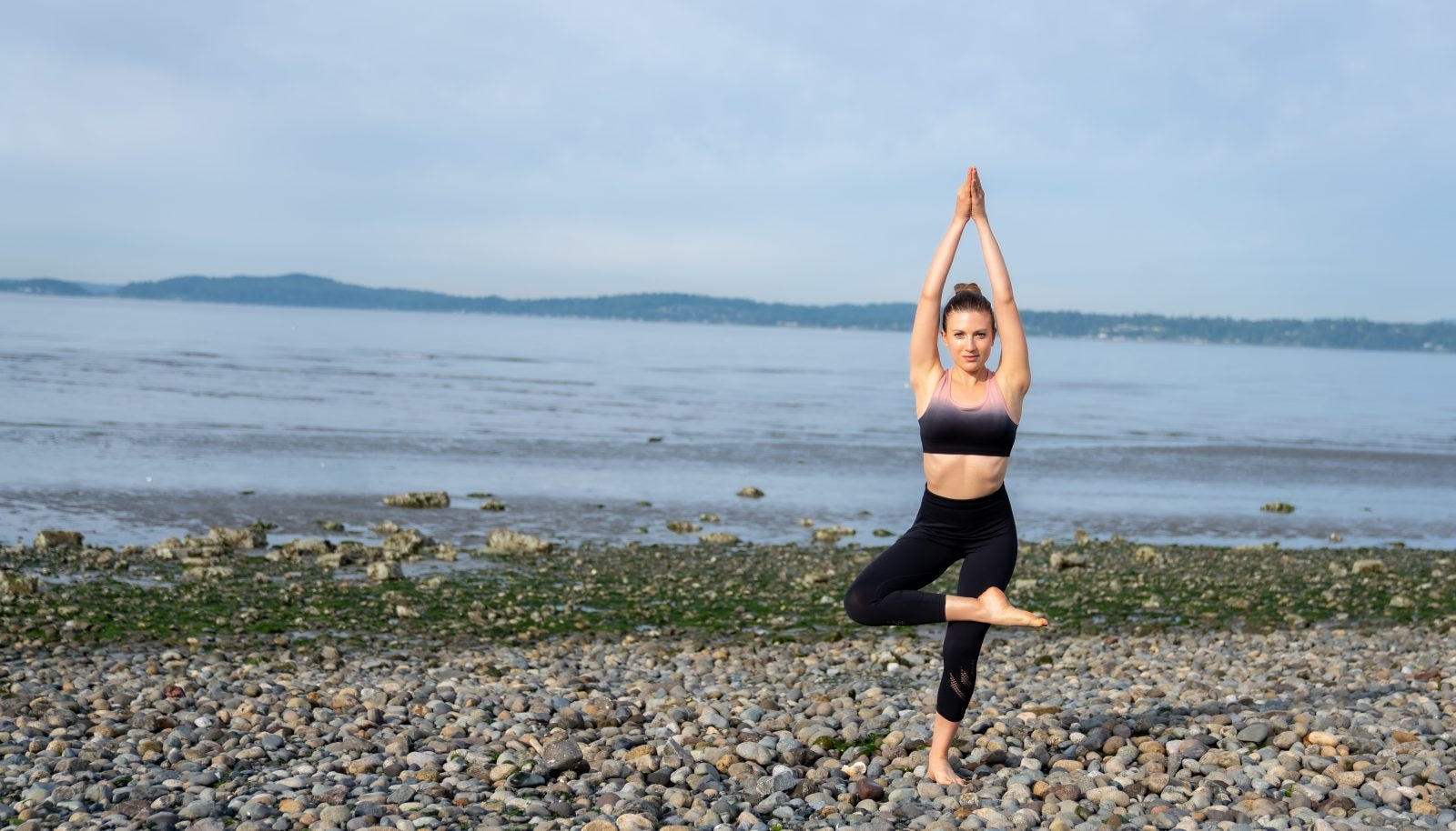 A woman in a yoga pose on a pebbled beach.