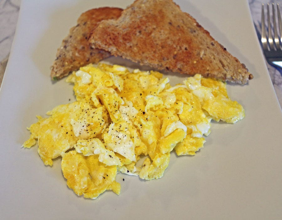 A plate of hard scrambled eggs with multigrain toast.