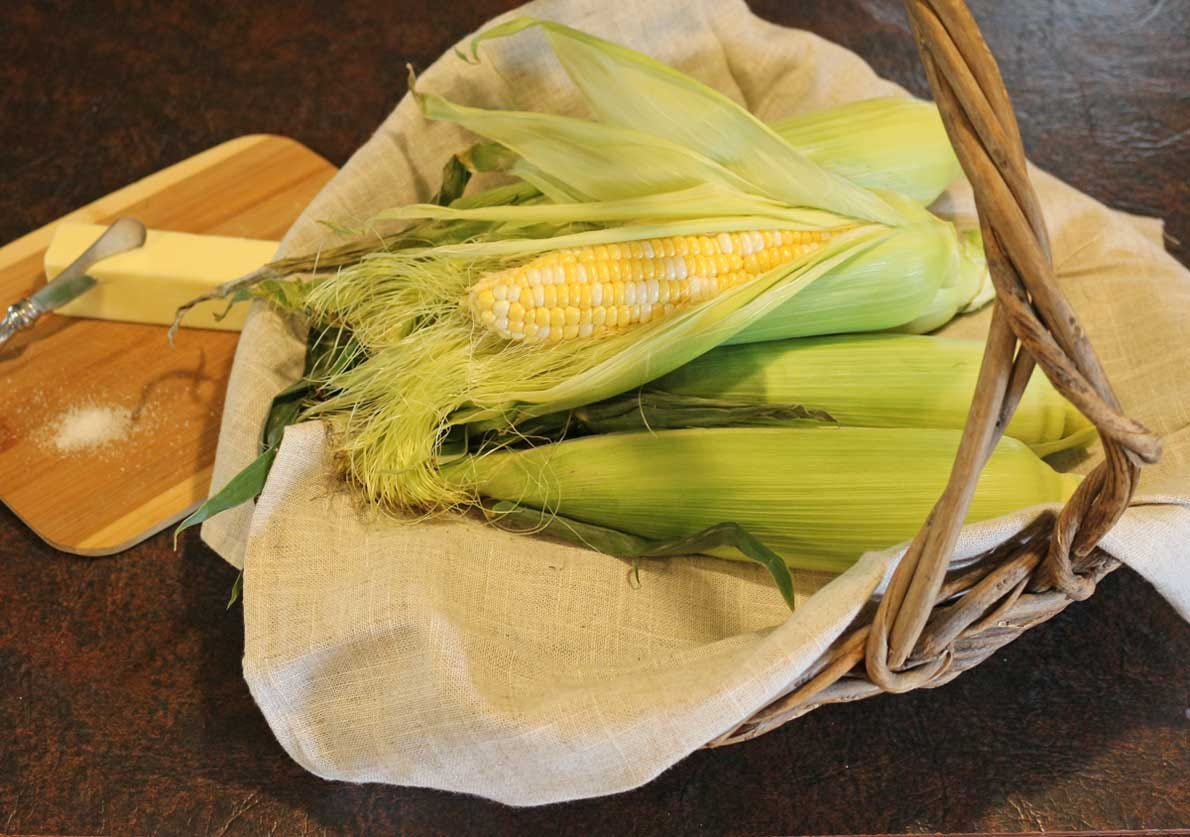 Corn on the cob in a basket, with butter and kosher salt on the side.