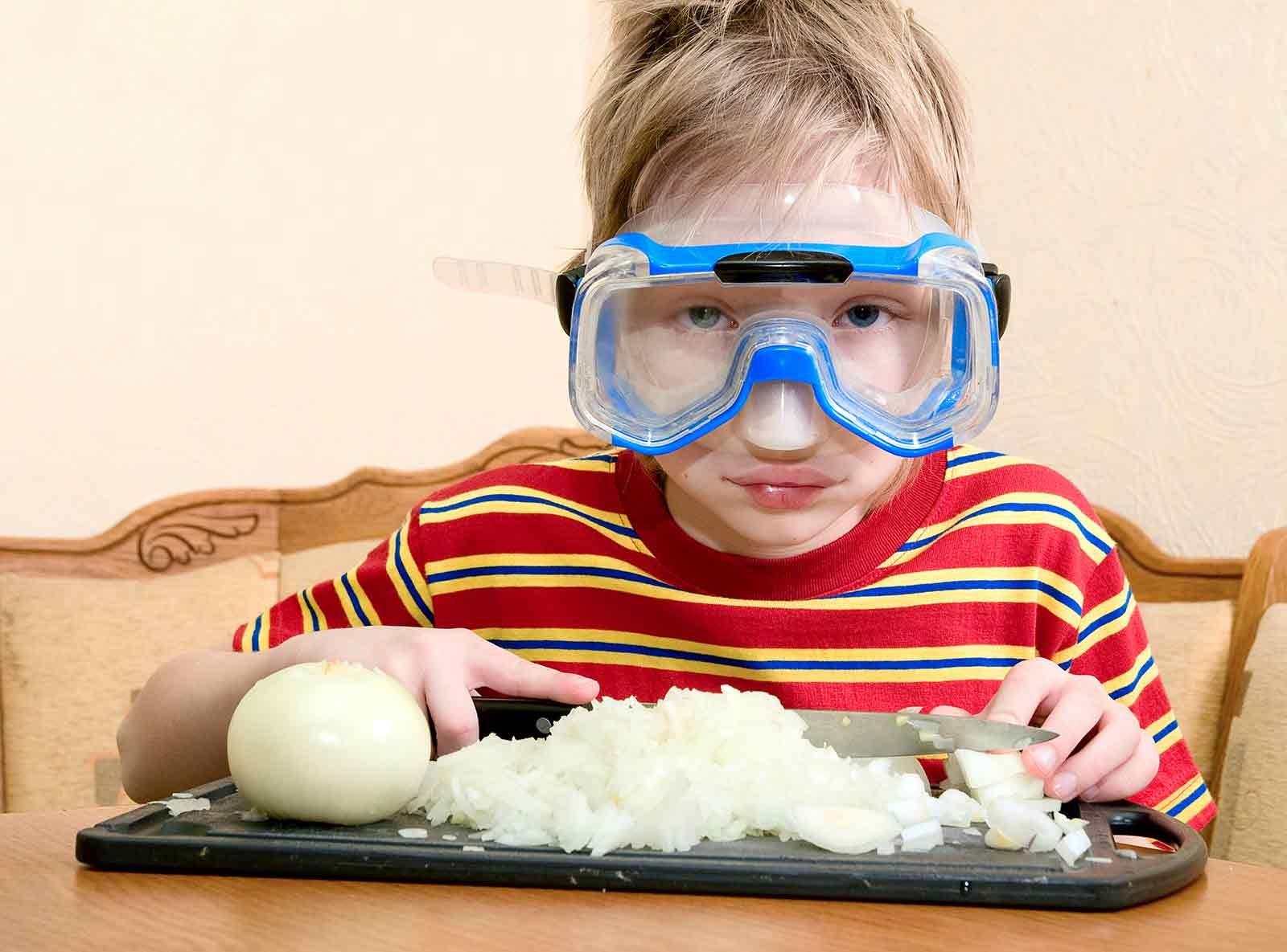 child cutting an onion wearing a snorkel mask