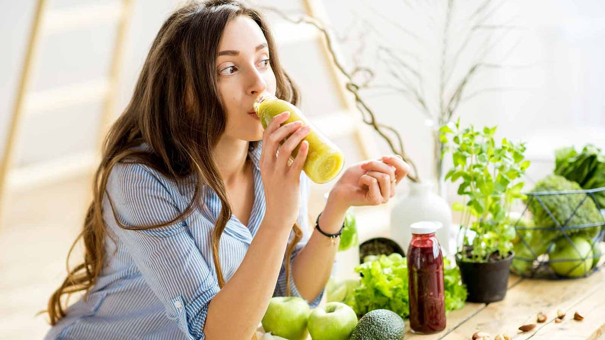 woman drinking a healthy green smoothie in a sunlight room surrounded by vegetables and fruit