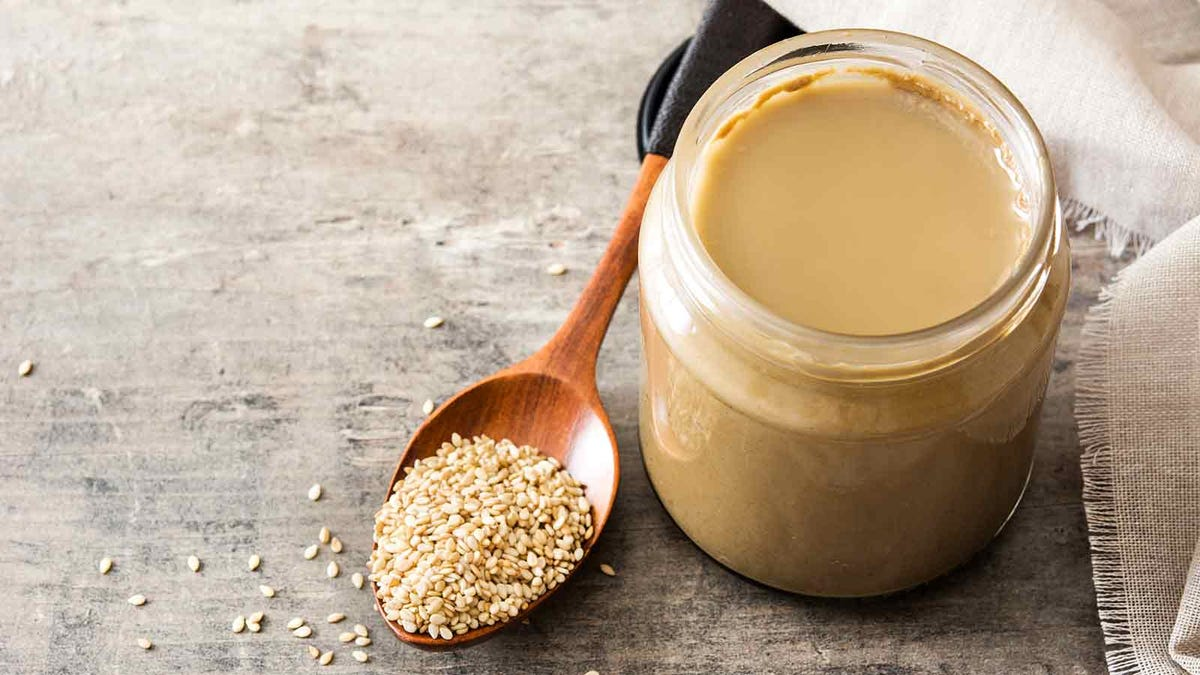 a jar of fresh tahini next to a wooden spoon laden with sesame seeds