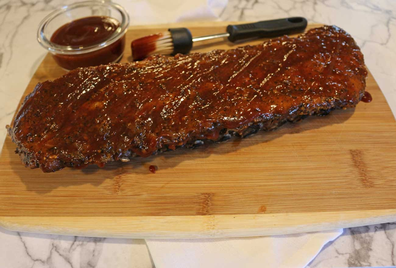 Full rack of ribs sitting next to a small dish of barbecue sauce and a brush.