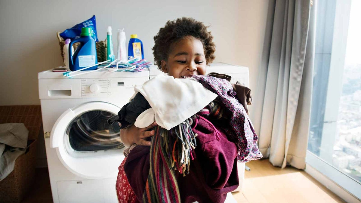 elementary age child helping unload the dryer and carry clothes