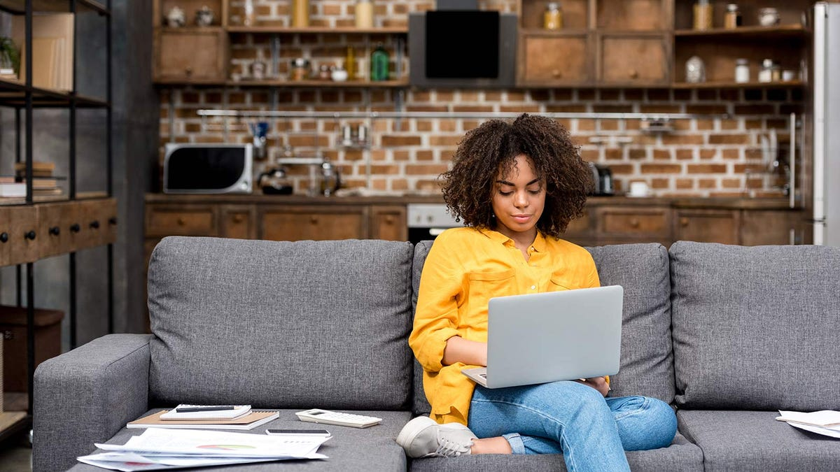 Woman working from home with her laptop on her living room couch.