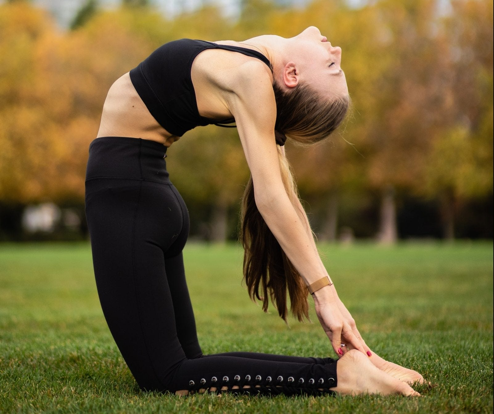 Woman doing yoga camel pose in a park