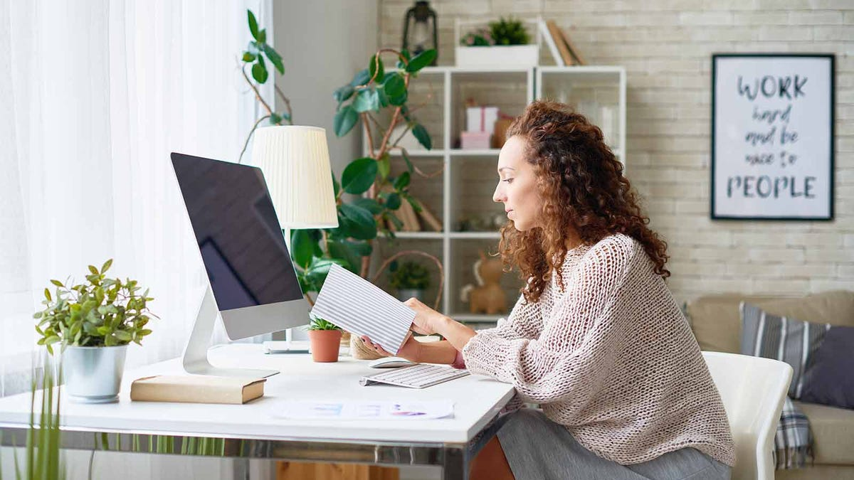 woman checking her planner while sitting in her sunlight home office