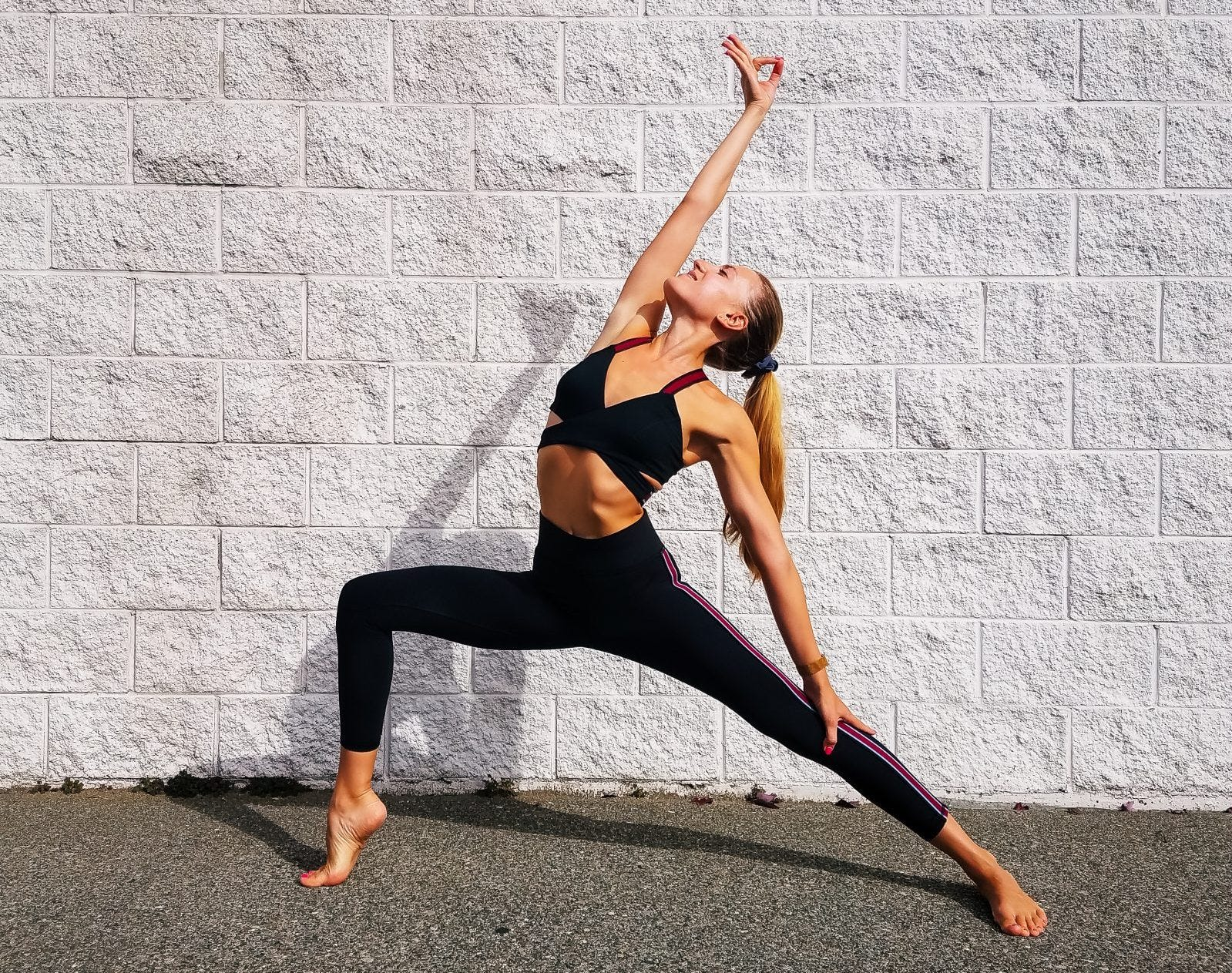 Woman doing reversed warrior yoga pose in front of a white brick wall