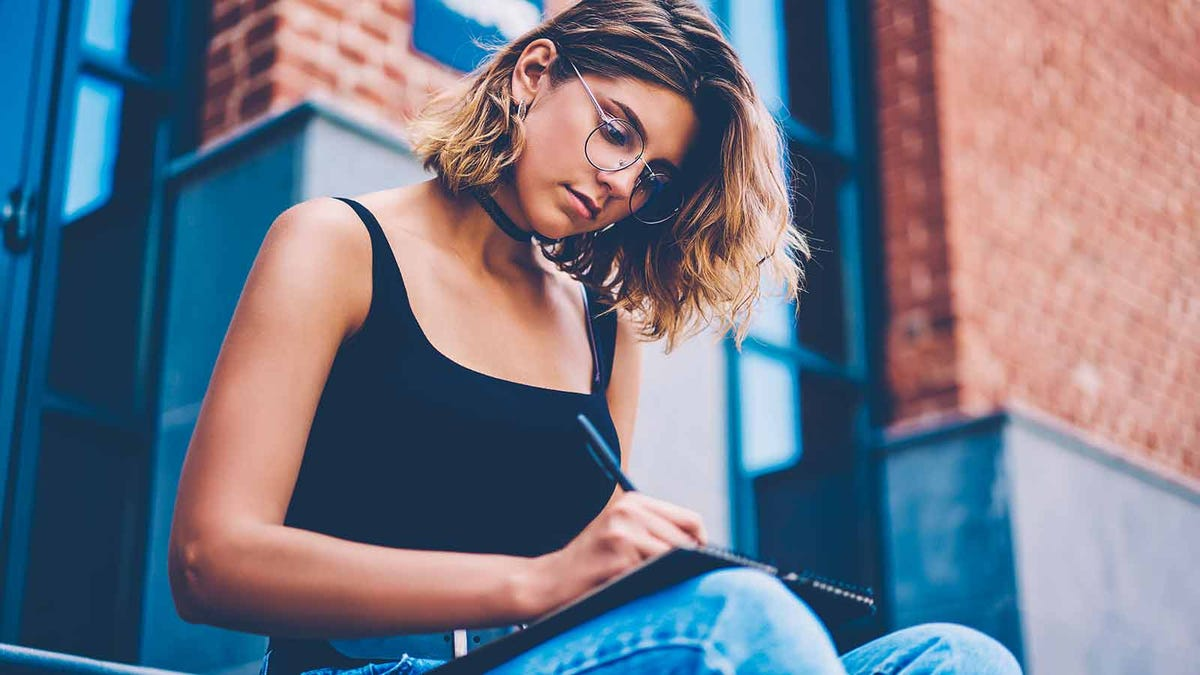 A young woman sitting on a stoop writing in a notepad.