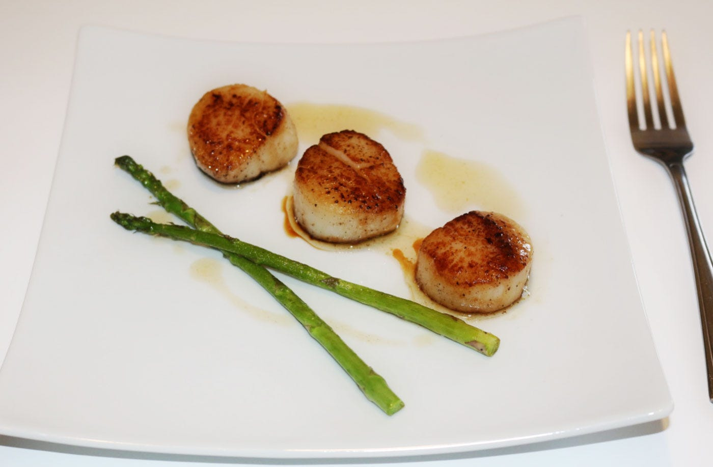 Three scallops and two pieces of asparagus finished with brown butter on a plate.