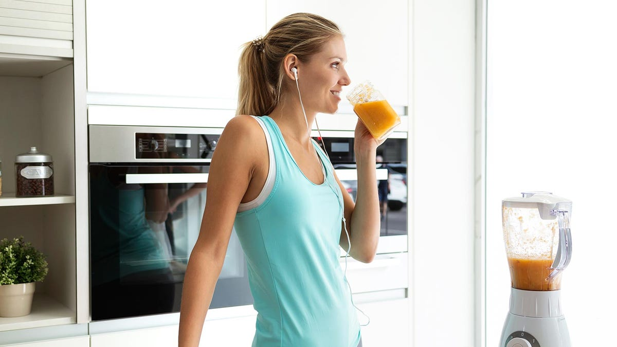 A woman wearing earbuds and drinking a smoothie in a kitchen.