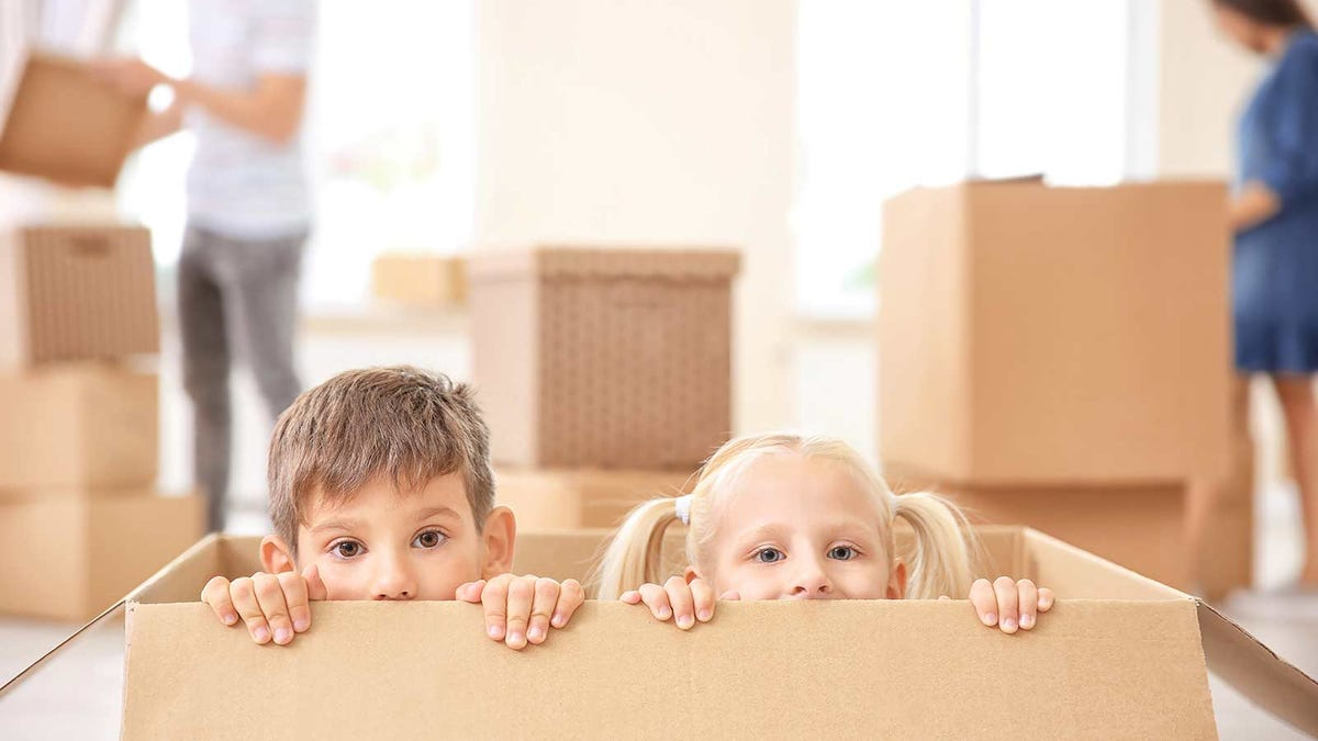 kids peaking out of a box as their parents pack up for a move