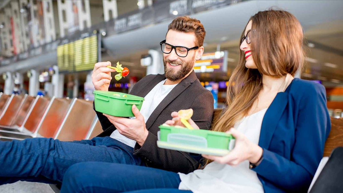 A couple eating salads at the airport.