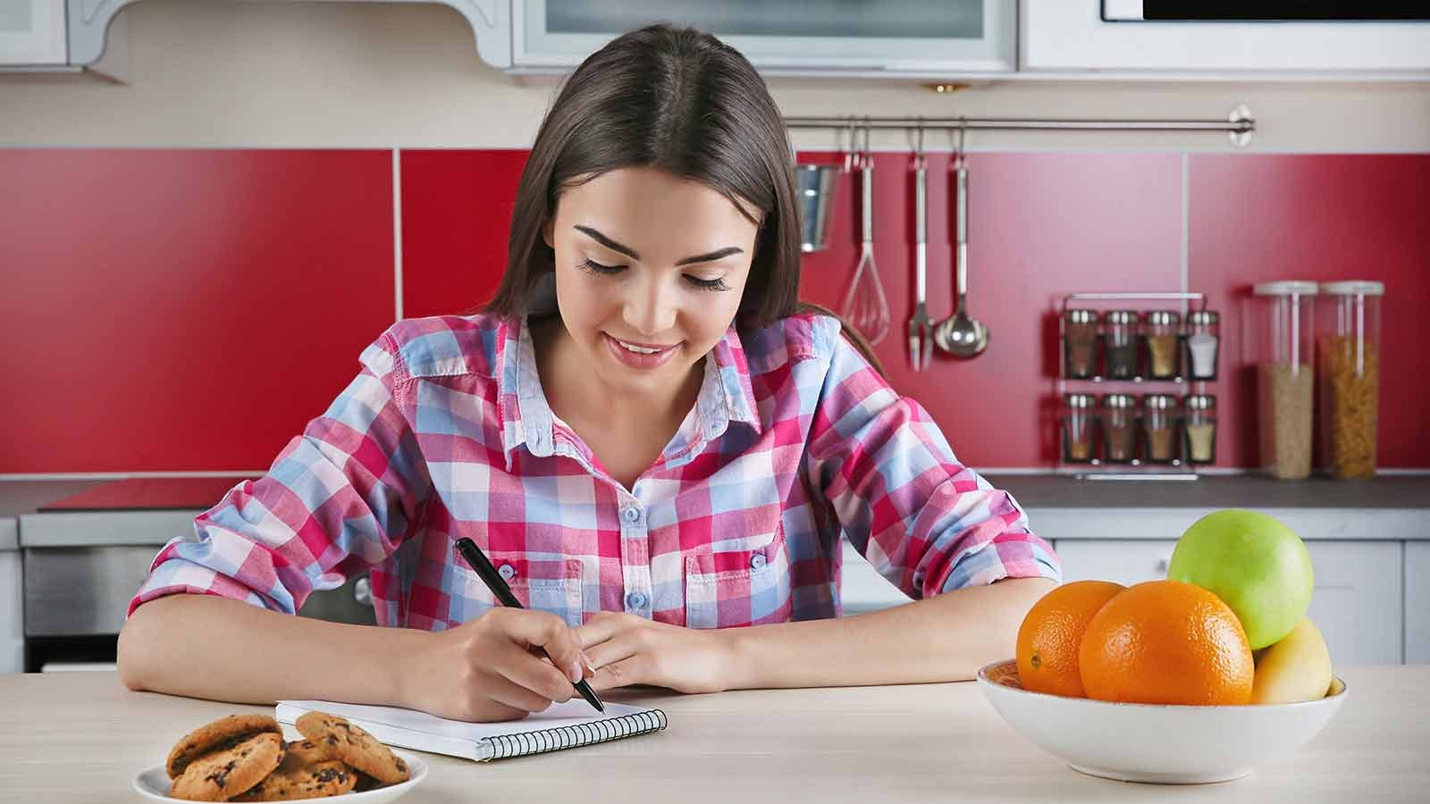woman writing in a food journal