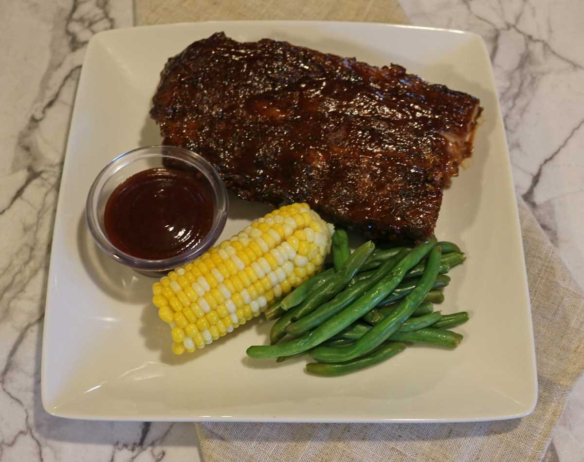 Half a rack of ribs on a plate with green beans, corn on the cob, and a side of barbecue sauce.