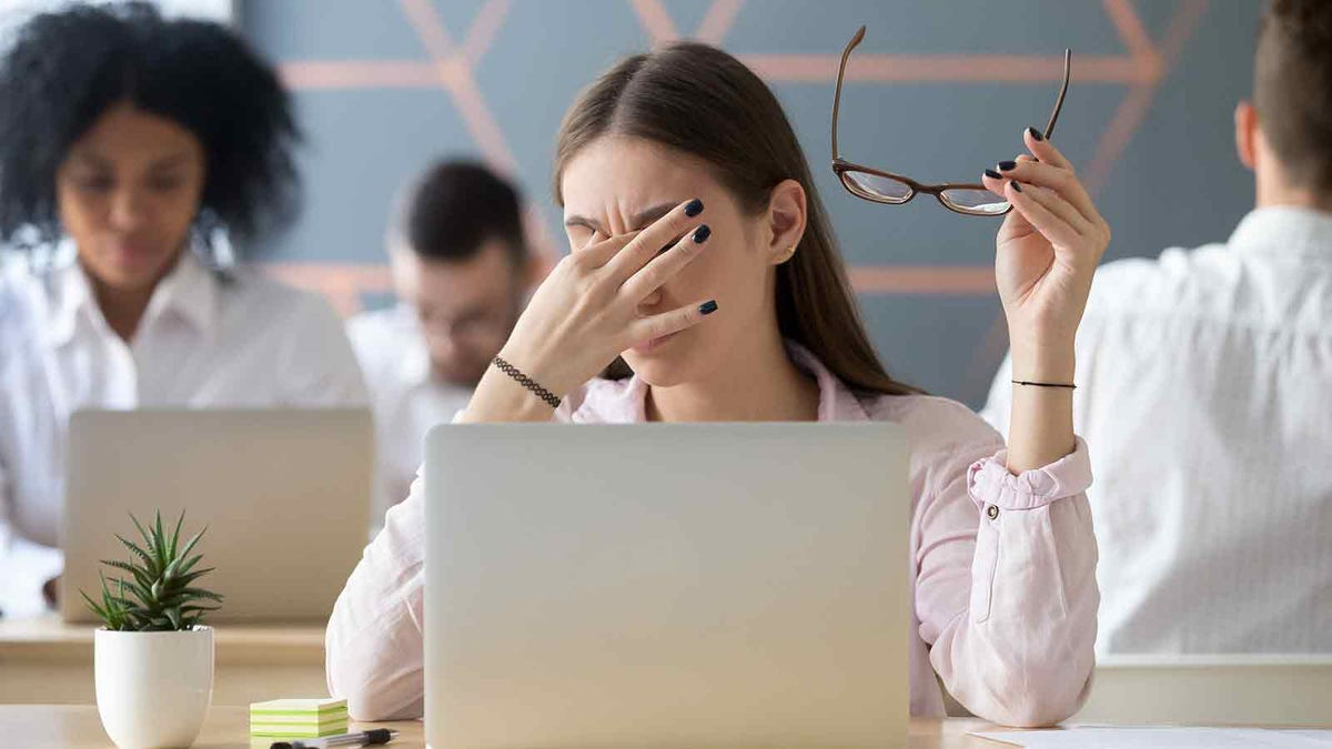 woman with eye strain from working on the computer too long, rubbing her eyes