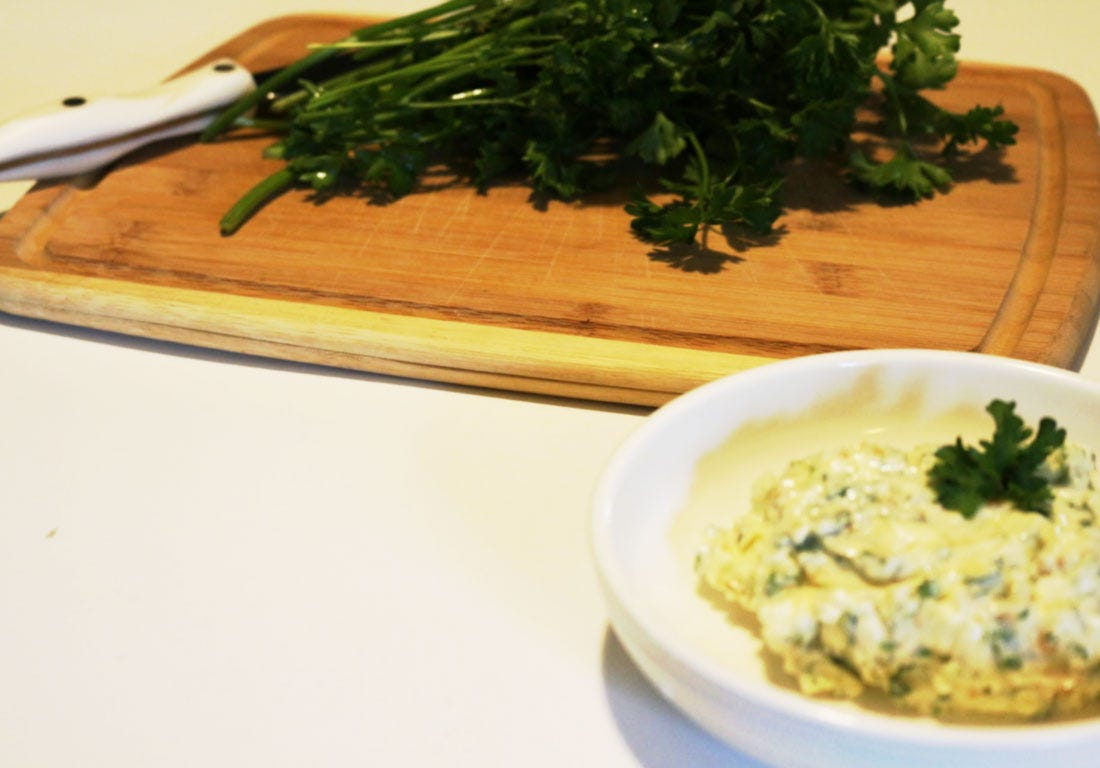 A bowl of garlic and herb butter next to a cutting board, with parsley and a knife on top.