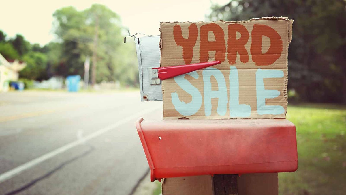 A cardboard yard sale sign stuck to the side of a mailbox.
