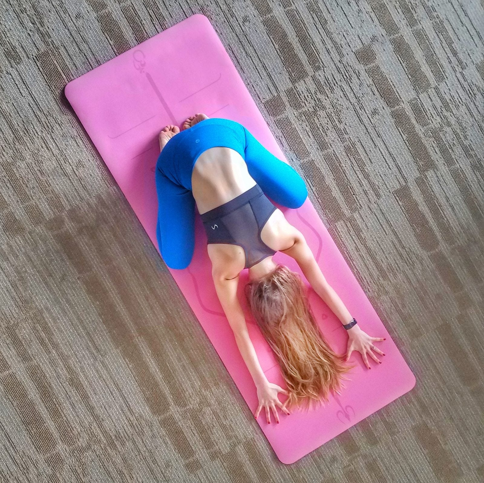 A woman in child's pose on a pink yoga mat.