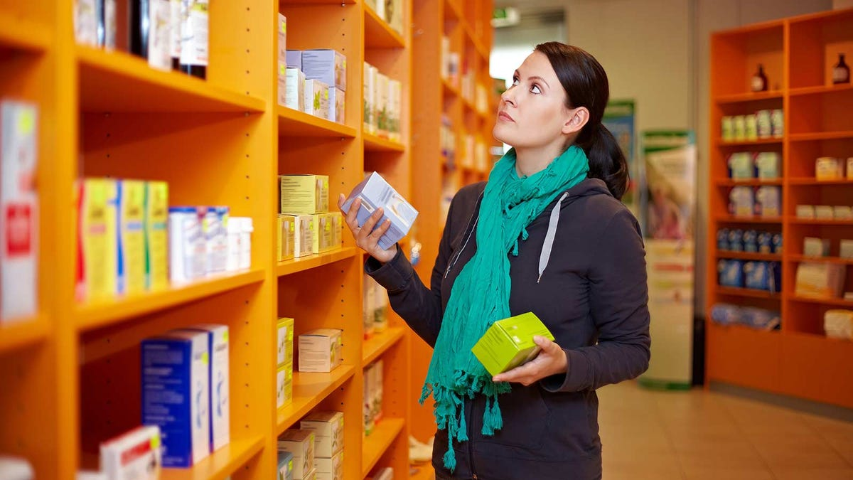 woman shopping for cold medicines in the pharmacy aisle