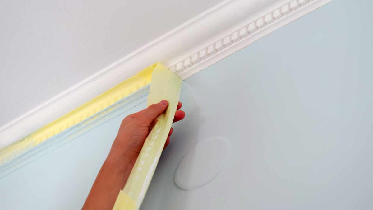 person peeling painter's tape off the molding in a freshly painted room