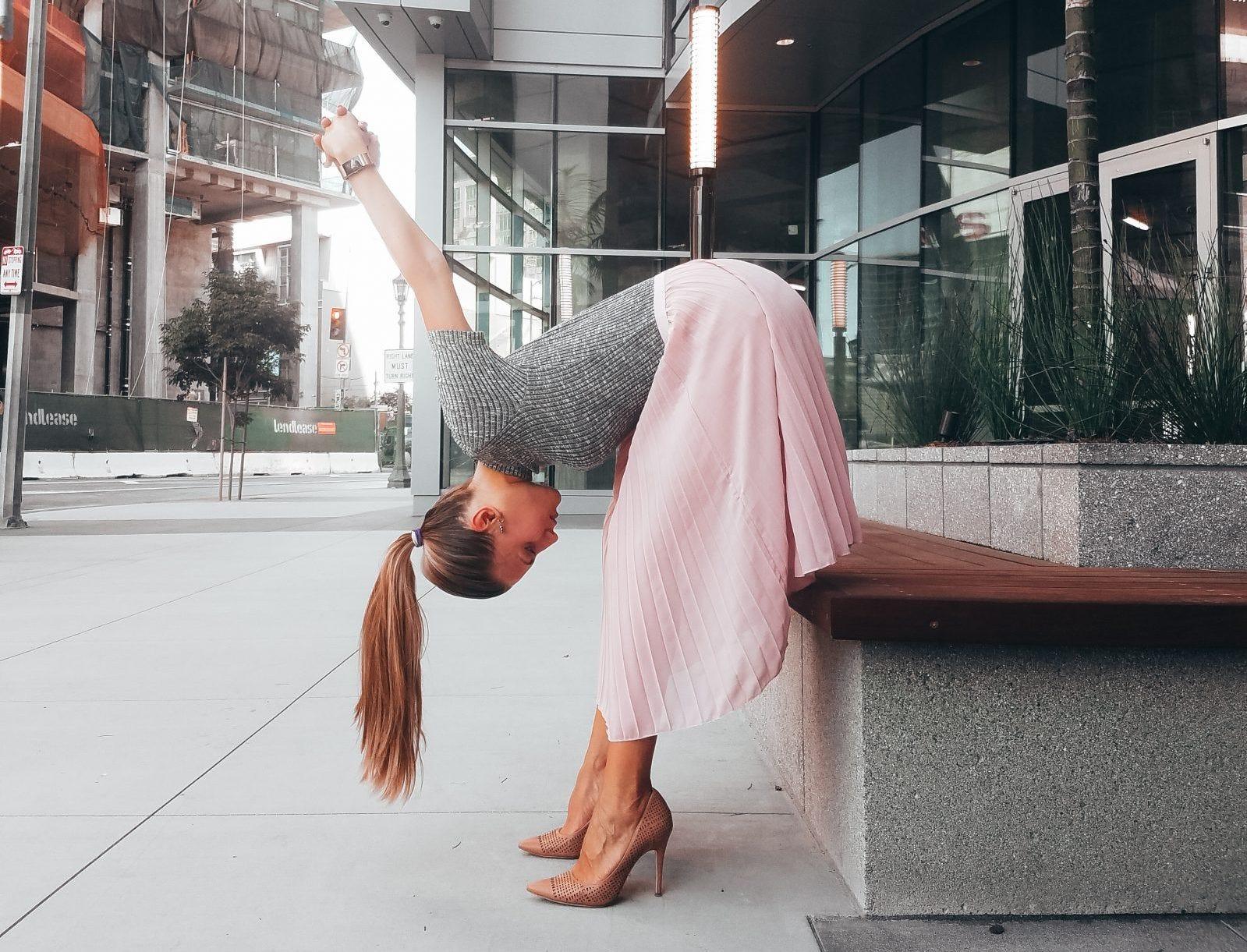 a young woman does a forward fold yoga stretch