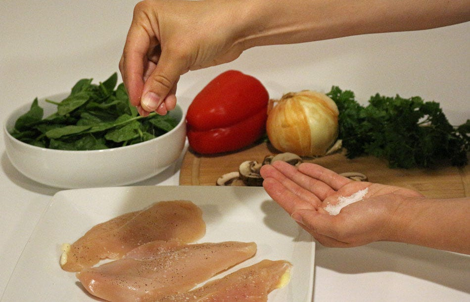 Sprinkling kosher salt on raw chicken breast with vegetables in the background.