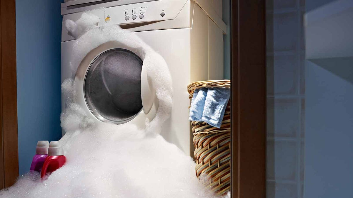 a high-efficiency washing machine flooding the laundry room with suds