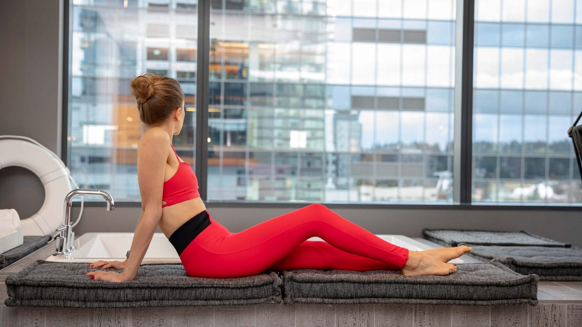 A woman in workout clothes relaxing next to a sunken tub and window.