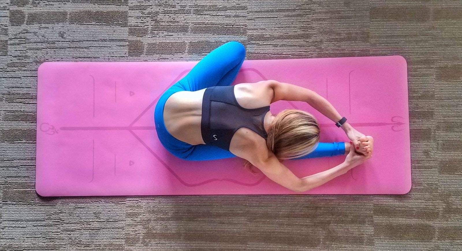 A woman doing a seated one-leg forward fold on a pink yoga mat.