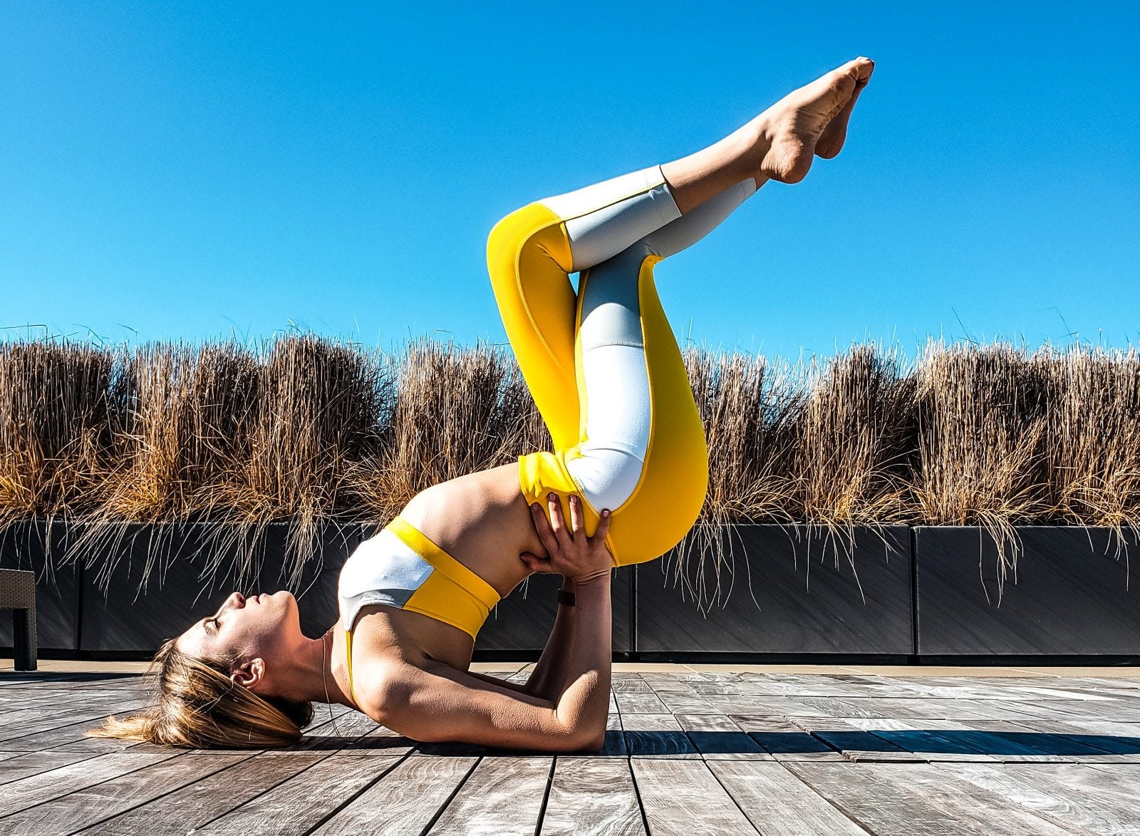 A woman doing a shoulder stand stretch outside.