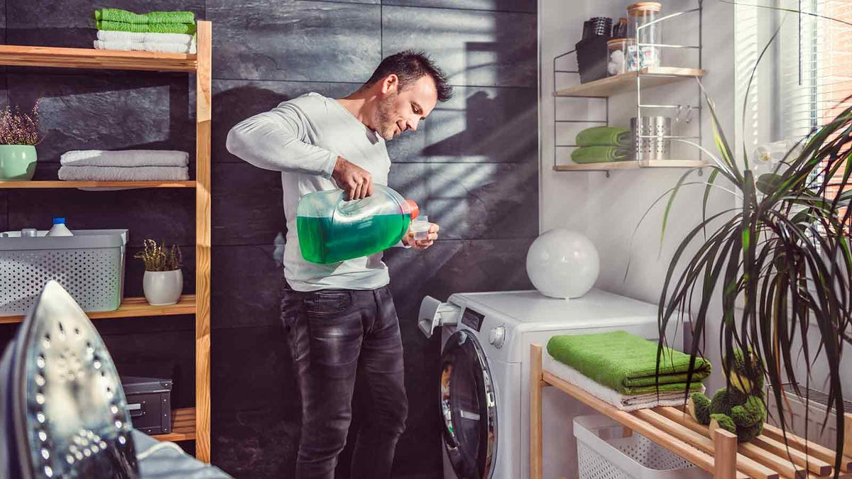 Man pouring laundry detergent into a measuring cup