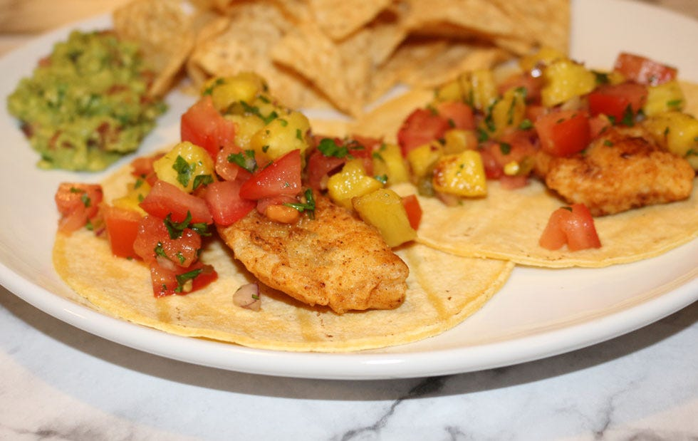Fish tacos topped with a pineapple pico de gallo served with chips and guacamole.