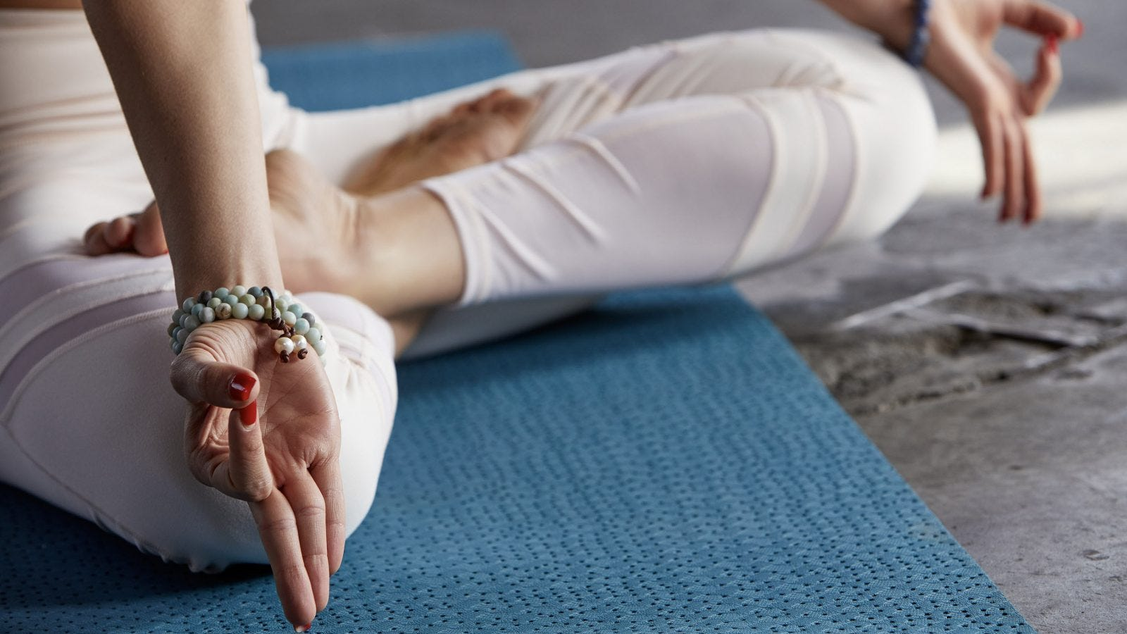 A woman's legs and hands in a yoga pose.