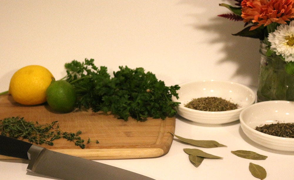 Fresh and dried herbs including parsley, thyme, basil, oregano, and bay leaves