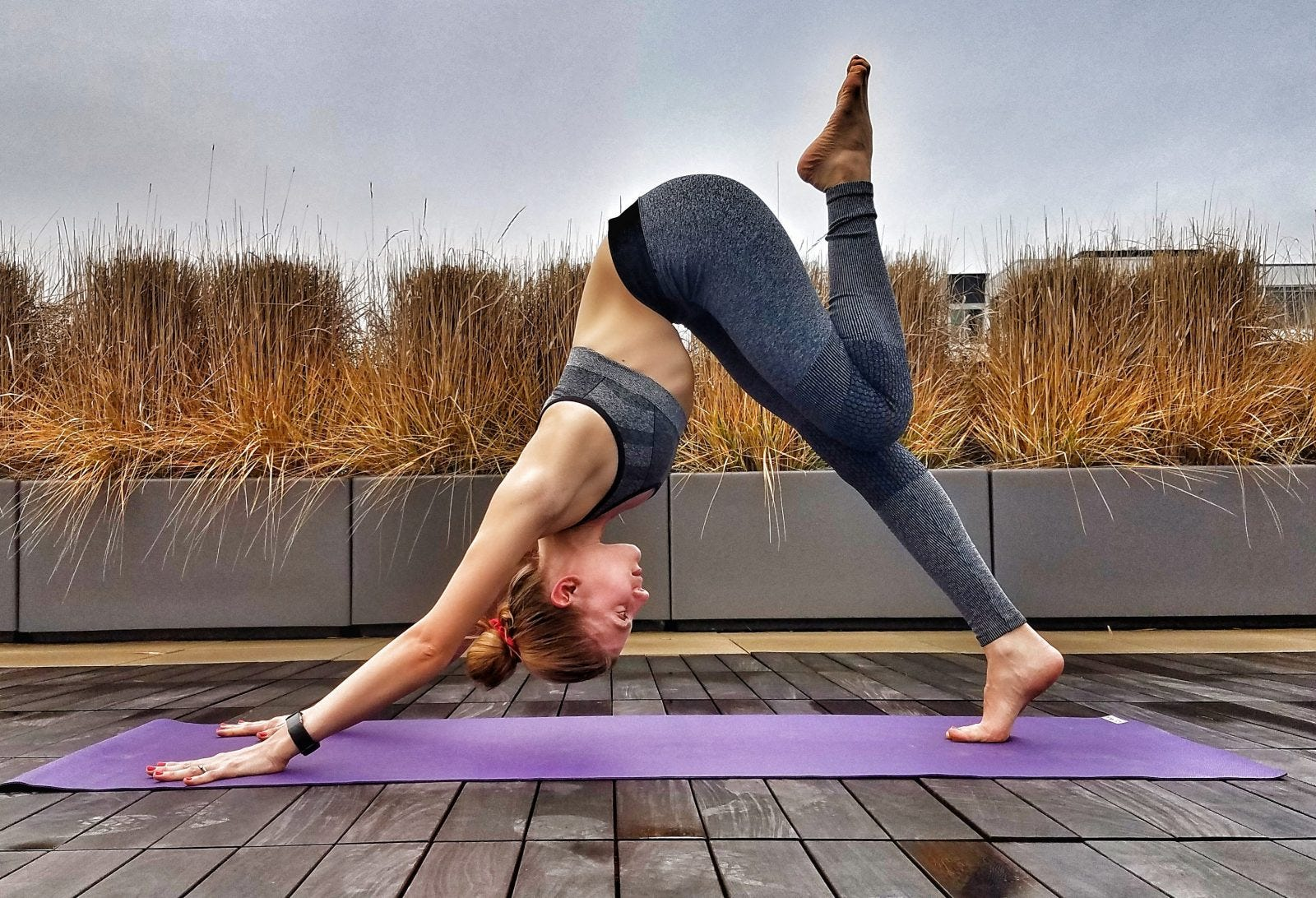 A woman doing a downward-facing dog yoga pose outdoors on a purple mat.