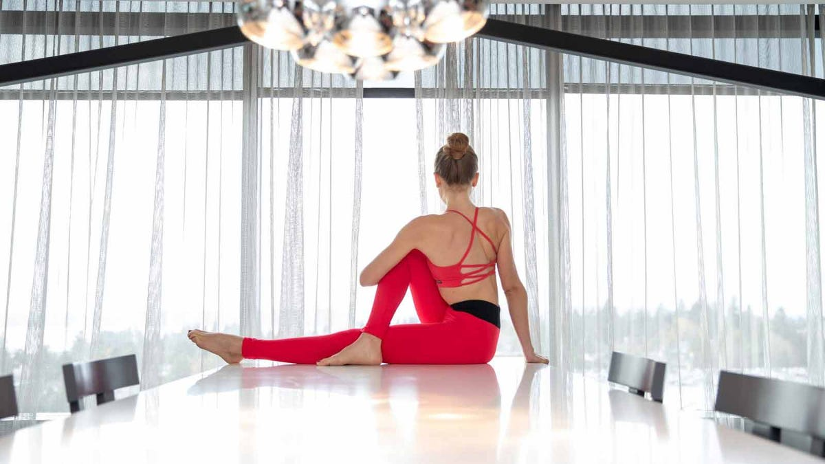 a young woman does a yoga twist on an office conference table