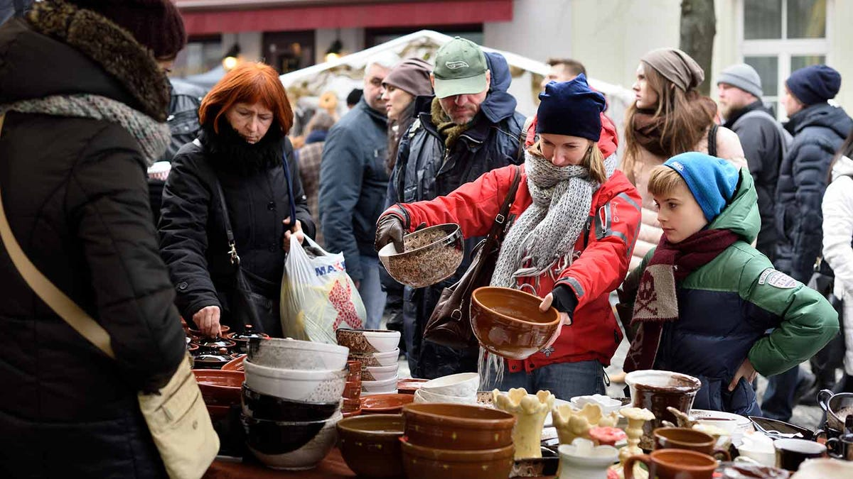 A woman comparing bowls at a crowded open air market.
