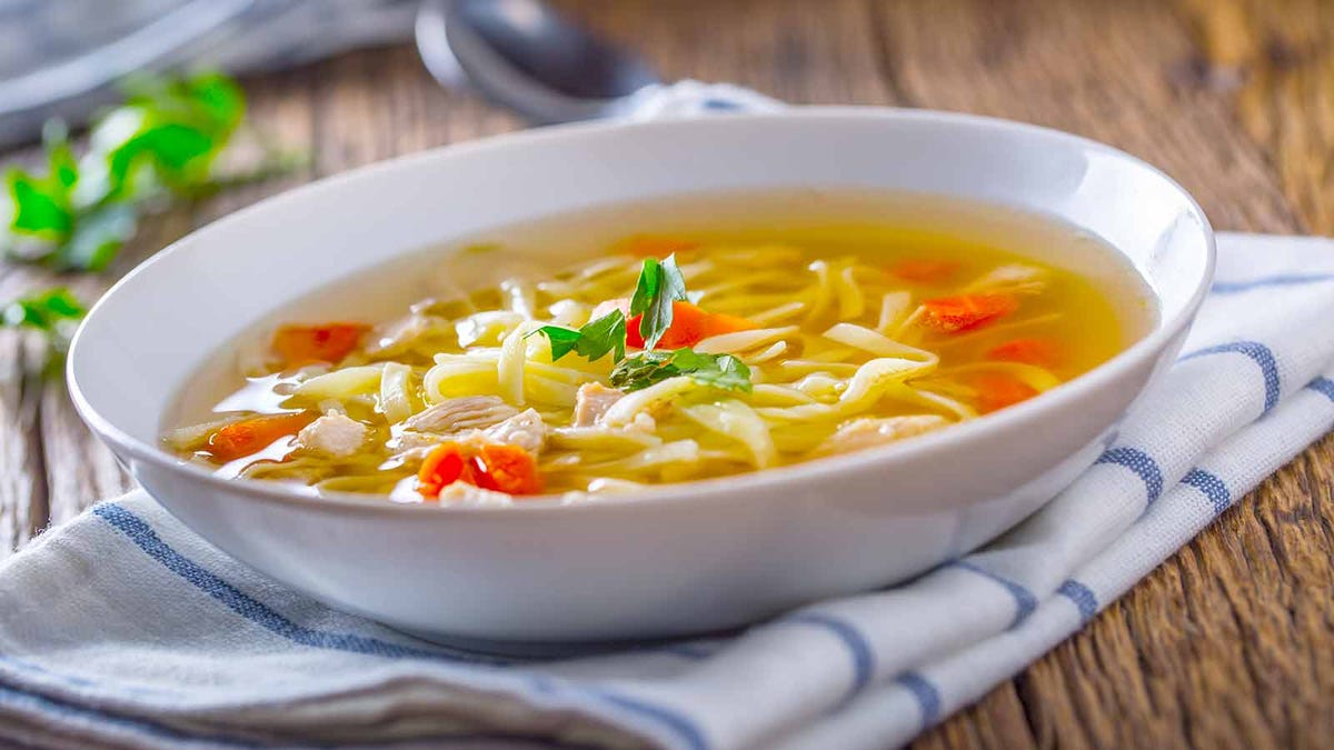 a delicious bowl of homemade chicken soup in a white bowl