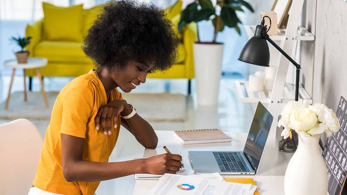 woman happily working from home in a sunny and colorful apartment