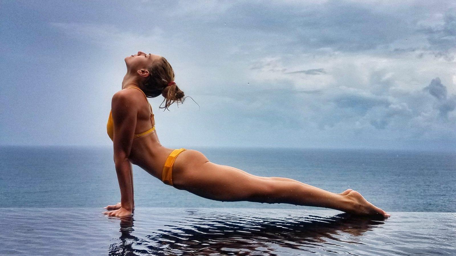 Woman doing upward facing dog yoga pose on the edge of an infinity pool