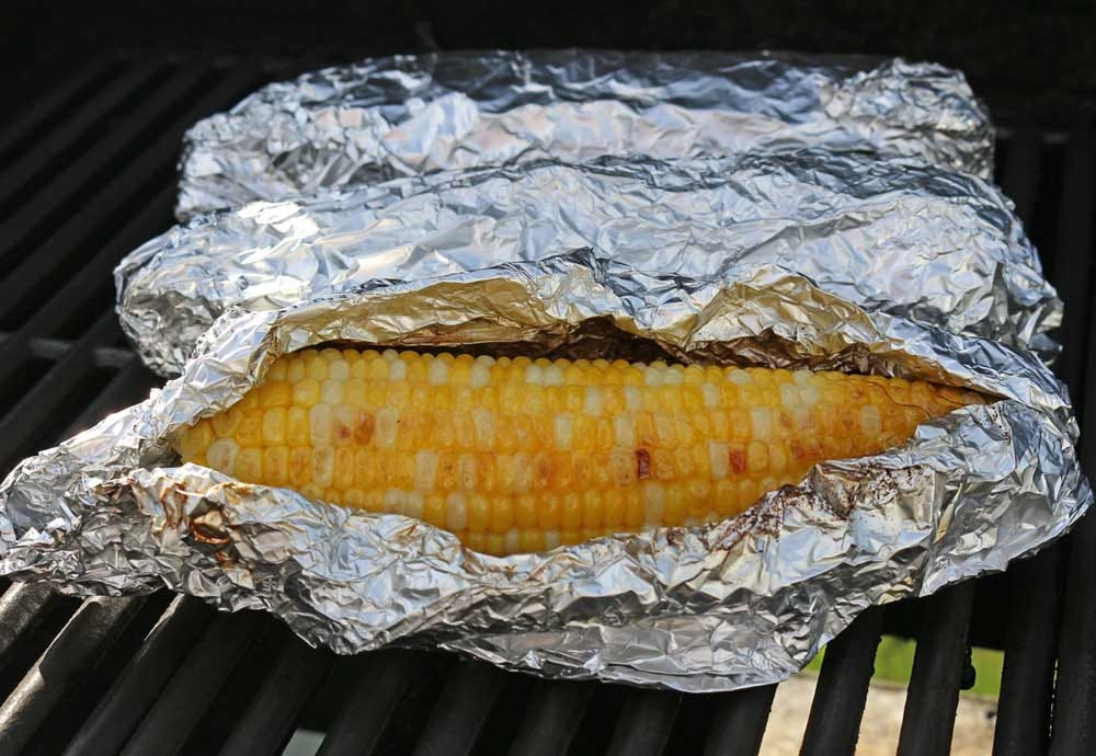 Grilling corn on the cob covered in aluminum foil