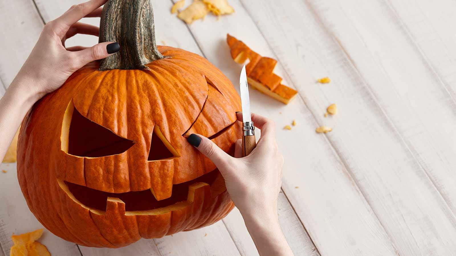 A woman's hands carving a jack-o'-lantern.