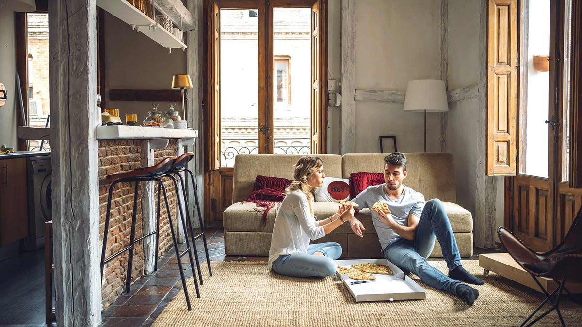 A man and woman eating pizza on a living room floor.
