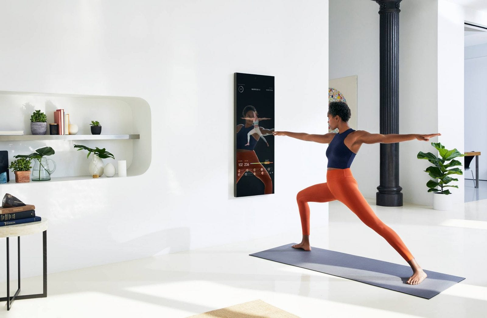 A woman doing a mirror workout in her living room.