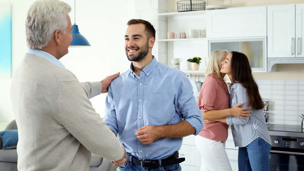 Two men shaking hands and two women hugging in a kitchen.