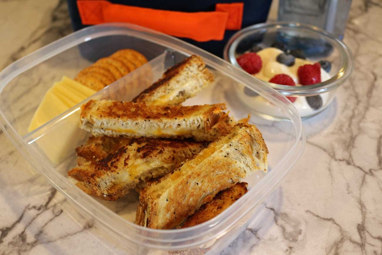 Grilled Cheese bites with cheese and crackers, and a fruit yogurt bowl.