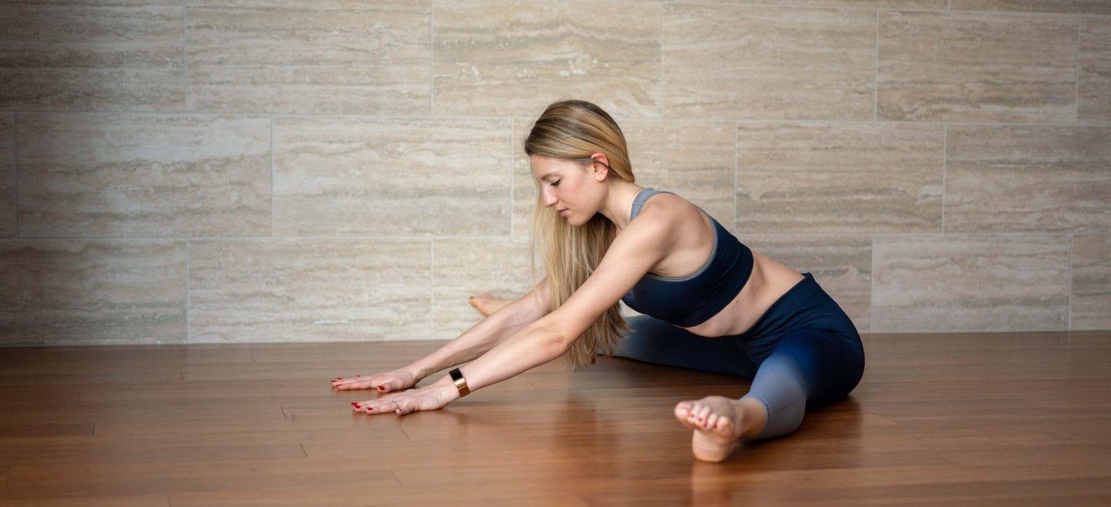 Woman doing seated wide-legged forward fold